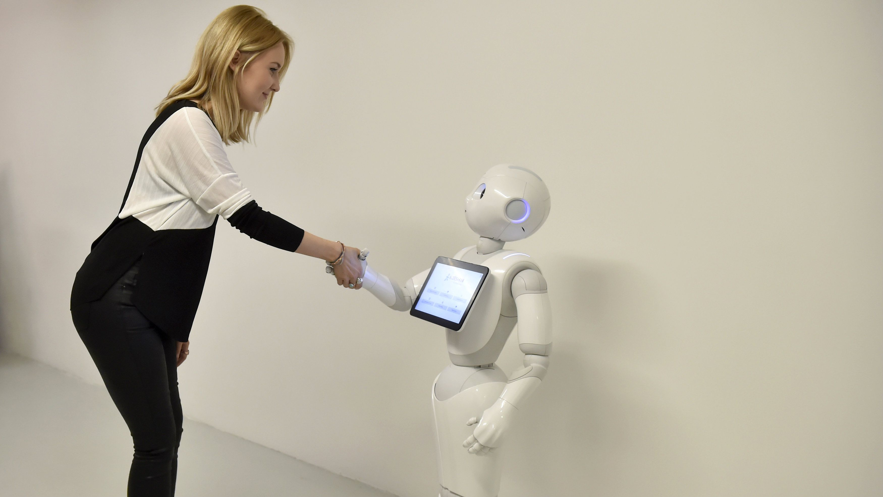 A press officer poses with 'Pepper' the Humanoid Robot at the 'World of Me: Store of the near future installation' in London, Britain, April 13, 2016.
