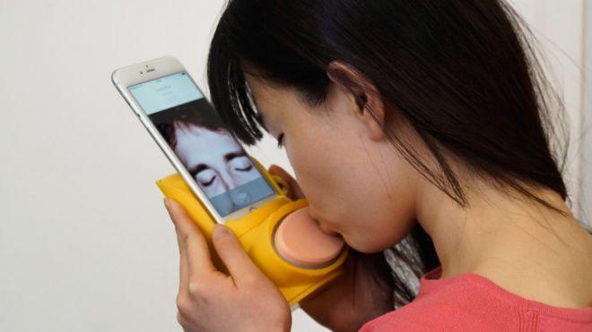Una mujer besa el dispositivo